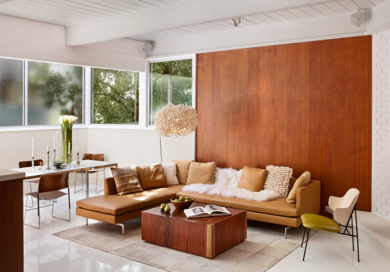 mid century modern living space L shaped sectional sofa in light brown light brown leather throw pillows compact wood coffee table