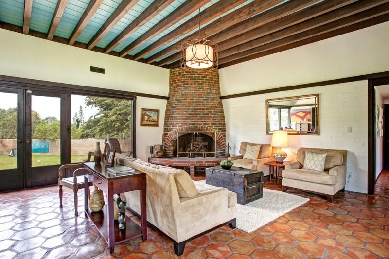 mid century modern living space idea light beige velvet sofas dark & shabby wood coffee table terracotta floors corner fireplace with red bricks surround
