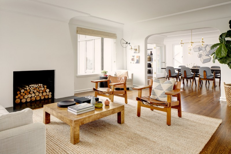 mid century modern wood living room set modern fireplace with plaster surround clean white walls light brown area rug medium toned wood floors