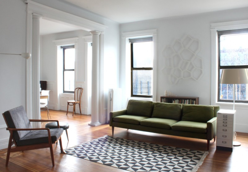midcenterury modern style living room green sofa dark grey chair with wood frame black white linen rug vertical drawer system in white medium toned wood floors