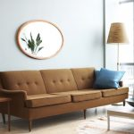 Mocca Toned Sofa Solid Dark Blue Throw Pillows Blue Chair Low Legs Coffee Table With Light Brown Top Square Shaped Wood Top Side Table With Brown Table Lamp Oval Shaped Wall Mirror With Wood Frame