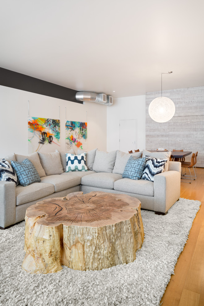 modern living room idea L shaped sectional sofa in grey multicolored throw pillows large tree trunk coffee table white shag rug medium toned wood floors