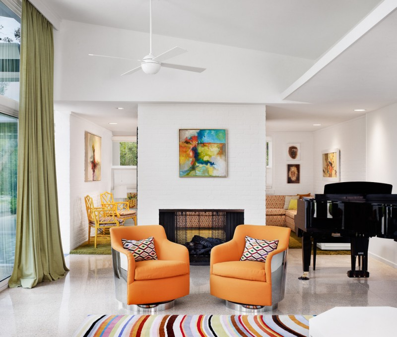 orange armchairs with multicolored accent pillows multicolored stripes area rug modern fireplace with white wall surround