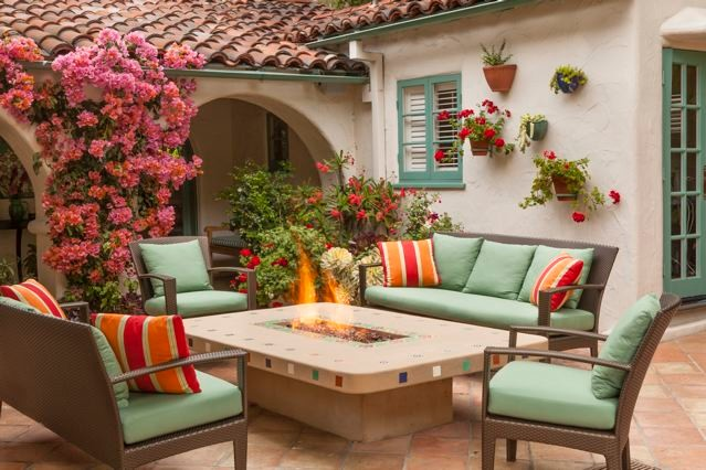 patio arched door roof green trim flowering firepit green cushions armchairs