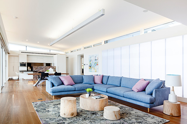 pop colored sectional sofa blue accent pillows pink accent pillows pale toned tree trunk coffee tables area rug with abstract style black accents tree trunk side table medium toned wood floors