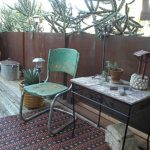 Retro & Industrial Style Front Porch Idea Old Industrial Chair Antique Side Table With Wood Top Dark Area Rug With Multicolored Motifs