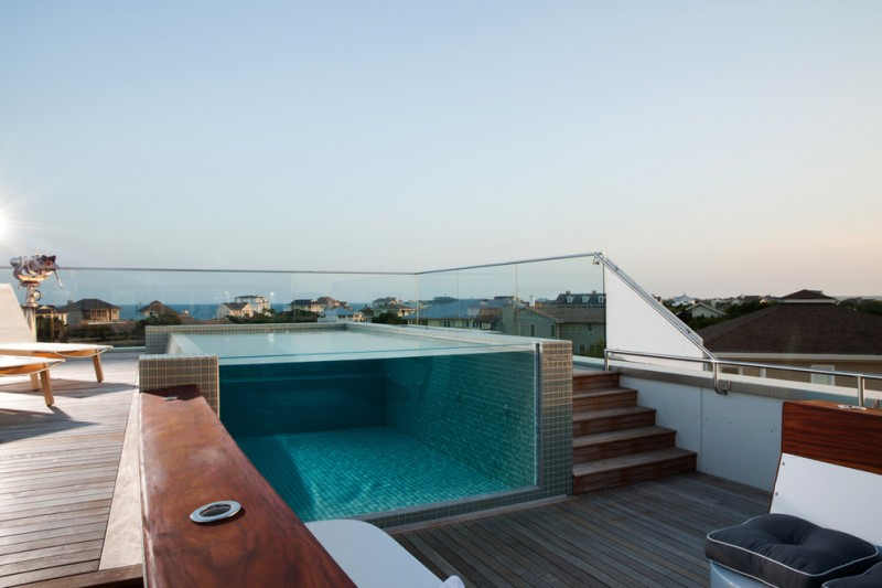 rooftop pool lounge chair wooden deck glass siding tiled wall