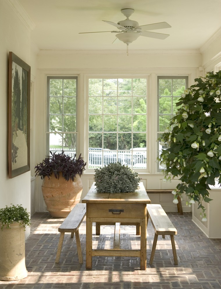 screened porch in white wooden rectangular shaped table two wooden benches pavers floors white ceiling fan big burnt clay vase with vivid plants