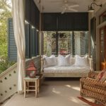 Shabby Chic Front Porch With Half Way Screen A Hanging Swing Daybed With White Accent Pillows A Rocking Chair With Multicolored Accent Pillow Small Side Table With Red Lighting Fixture