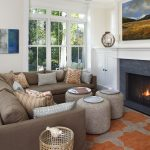 Small Living Room With Orange Grey Rug, Beige Corner Sofa Wih Pillows, Three Brown Ottoman With Tray For Coffee Tables