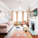 Small Living Room With Orange Rug, Soft Orange Gordyn, Soft Orange Velvet Sofa, Orange Chairs, White Ottoman, Clear Acrylic Coffee Table, White Shelves, Firepla
