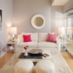 Small Living Room With White Poufs, Clear Acrilyc Chair, White Sofa, White Fur Rugs, White Coffee Table, White Side Tables With White Table Lamps