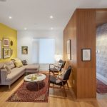 Small Livingroom With Wooden Wall, Yellow Wall, White Wall With Distorted Glass Window, Beige Corner Sofa, White Round Coffee Table, Red Rug, Black Chairs