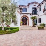 Stone Paving Palm Tree Entry Stairs Arched Dorrway Arched Window Glass Door Wall Sconce Balcony Brick Accent