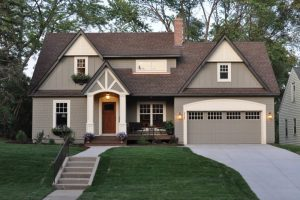 timeless wood exterior home with a gable roof stair pathway green grass lawn gray garage doors brown front door glass windows white trim