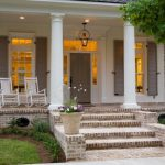 Traditional Porch Idea White Rocking Chairs White Exterior Pillars Exterior Windows With Grey Shutters Grey Entrance Door Brick Paving Floors
