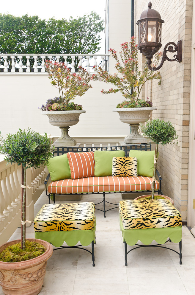 traditional porch idea wrought iron furniture set with orange and green comforters and pillows burnt clay vase for decorative plants classic wall lamp