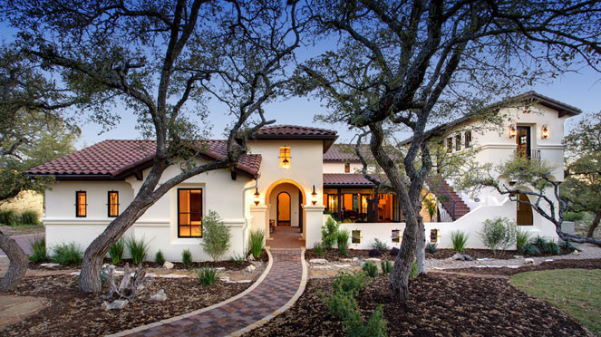 two storey house courtyard pathway arched door wall mounted lanterns tiled roof stairs stucco trees
