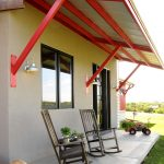 Urban Style Front Porch Idea Steel Awning Supported By Red Bars Two Wood Rocking Chairs Concrete Floors Concrete Walls Glass Windows With Black Trims