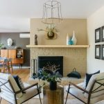 Warm And Cozy Fireplace Seats Fireplace With Clay Toned Surround Beige Chairs With Throw Pillows Tube Shaped Side Table Colorful Decorative Vases
