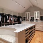 White Island Built In Closet Bench Open Shelves Marble Countertop Wooden Floor His And Hers Hanging Rods Track Lights White Cabinet Glass Cabinet