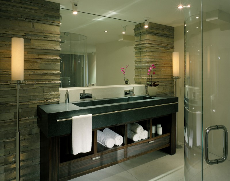 bathroom double sink granite countertops stone columns wall standing lamps sconces bathroom tiles floor glass door shower rectangular mirror door less cabinets