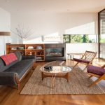 Dark Grey Smooth Lined Sofa Accompanied With Wooden Chairs With Simple Red Cushion