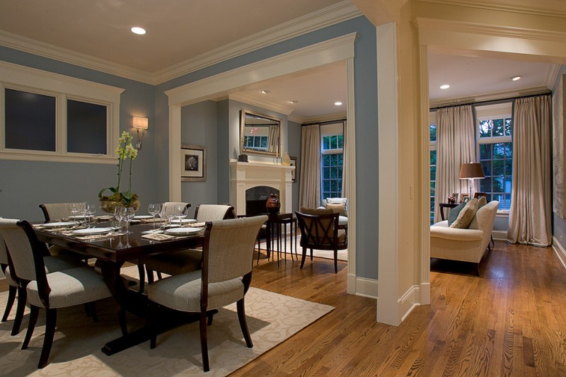 dining room with glass top wooden table and brownish grey chairs, open to living room with brown sofa and chairs, white fireplace