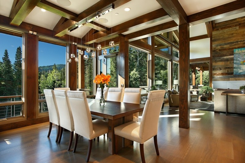 dining room with rectangular wooden table and beige leather chairs, open to living room with grey couches and grey rug