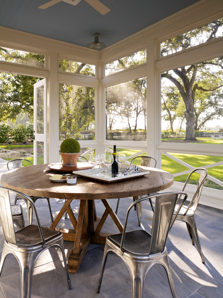 farmhouse porch with grey floor, blue wooden ceiling, white wooden framed glass window, round wooden table, metal chairs