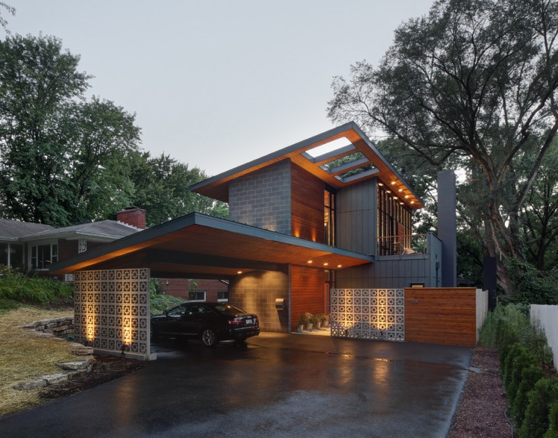 home with mid century exterior with grey side wall, wood isding on the front, slanting roof with three square holes, windows on front part