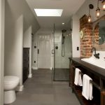 Large Industrial Master Gray Tile And Porcelain Tile Porcelain Floor Corner Shower With A Trough Sink, Open Cabinets, Dark Wood Cabinets, Engineered Quartz Countertops And Gray Walls