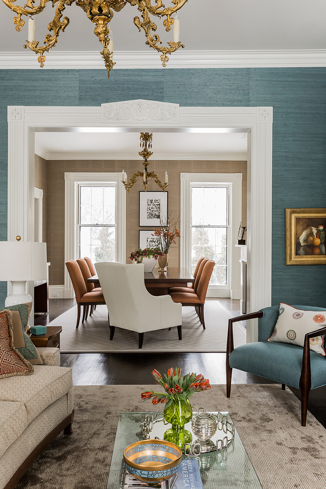 living room with brown sofa, blue chairs, rectangular glass top coffee table, brown rug, and dining room with rectangular wooden table with brown and white chairs