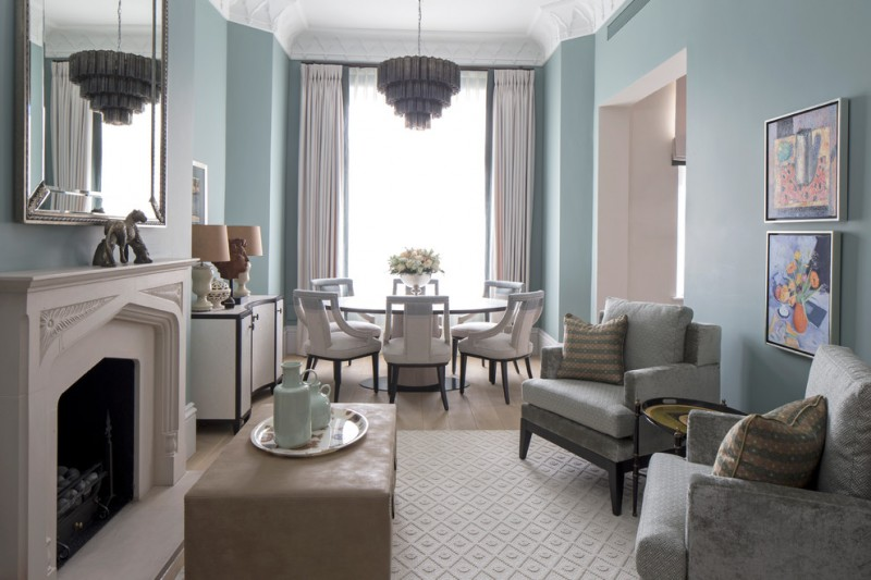 living room with grey couches with tray top side table and rectangular ottoman as coffe table combined with round dining table with white chiars