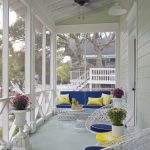 Long White Wooden Porch With Artistic White Wire Chairs, Sofa, White Wire Round Glass Top Table, With Blue Cushions, Yellow Pillows, Yellow Round Coffee Table,