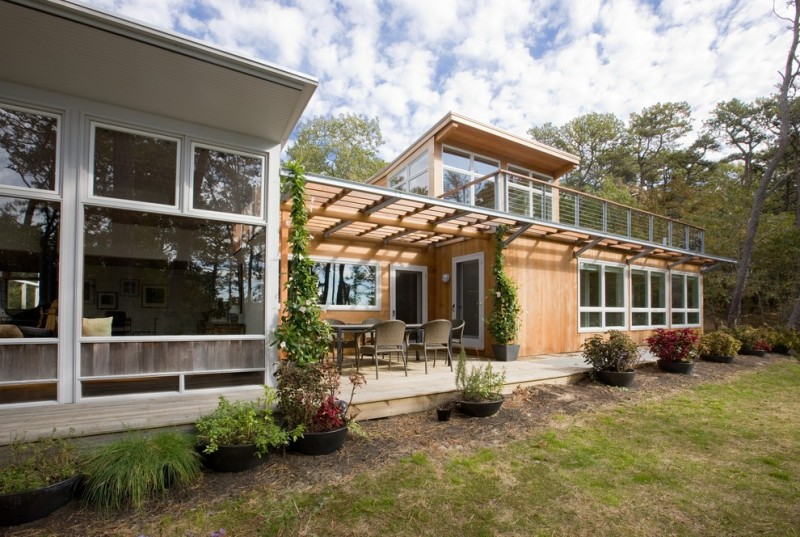 midcentury home with wooden wall part of the hosue and glass window part of the house, siding wood roof on the patio, second stoy with large glass windows