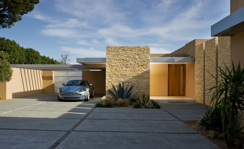 midcentury modern home with yellow textured wall, yellow painted wall, flat roofgrey concrete way,