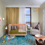 Nursery With Soft Beige Wall, Soft Grey Rug With Blue Pattern, Light Brown Crib, Soft Beige Chair, Wooden Shelf