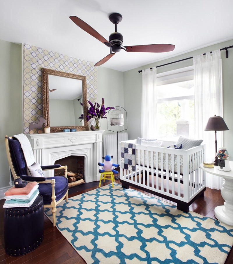 nursery with white wooden crib, grey wall, fireplace, blue velvet chairs, blue leathered ottoman, white side table with brown table lamp, white blue colored rug with plus s