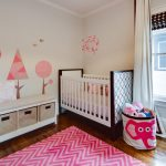 Nursery With Wooden Flooring, White Panted Wall, White And Dark Brown Wooden Crib, White Cabinet With Cushion On Top, Toys Keeping Bag, Pink Lined Spike Patterned Rug