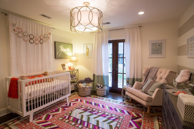 nursery with wooden flooring, white wall, white wide rocking chair, white crib, white shelves, white curtains, round pendant lamp with gold cage, pink patterned rug