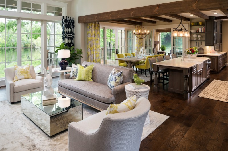 open living room with grey sofa set, rectangular mirrored glass surfaced coffee table, dining room with long wooden table with yellow chairs, kitchen with marble to