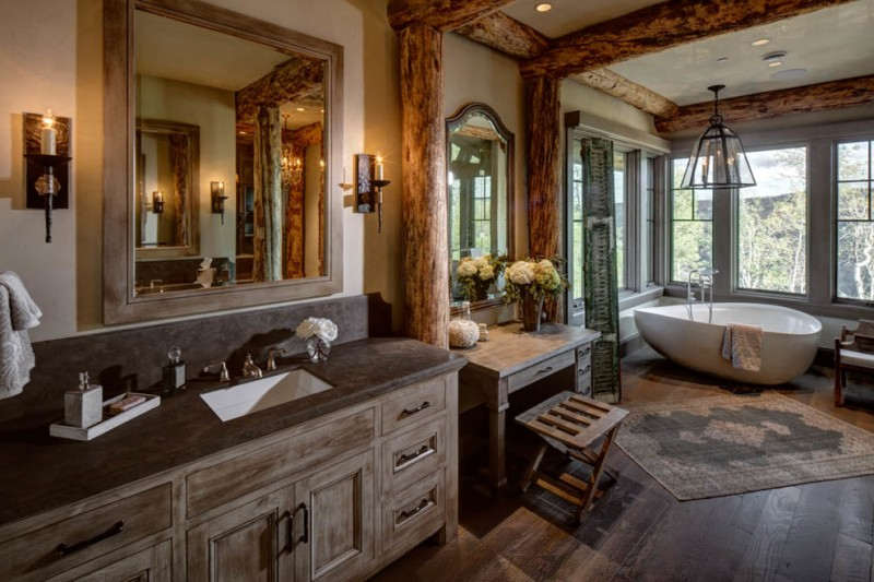 rustic vanity with grey marble top, square wooden framed mirror, accompanied with makeup counter on the left with wooden table and stool completed with high m