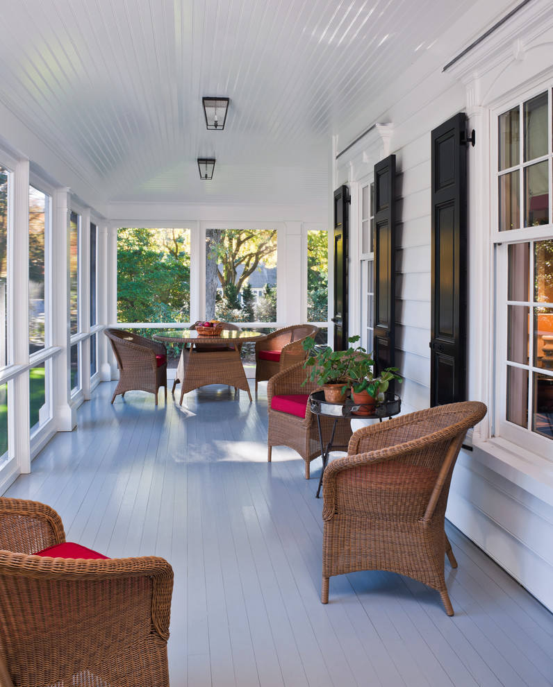 screened in porch with white wooden flooring and ceiling, glass window all over the wall with white wooden beams, rattan chairs with pink cushions, round rattan table