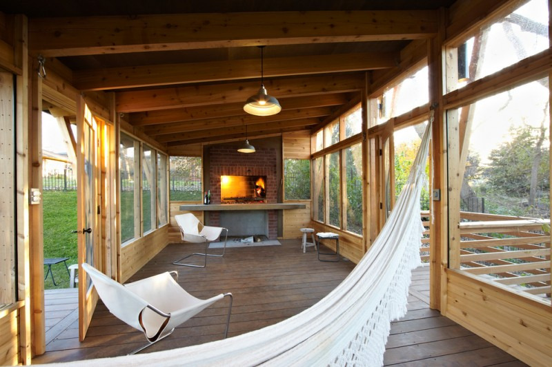 screened in porch with wooden floor, wall, ceiling, white chairs and hammock, brick fireplace, industrial pendant lamp