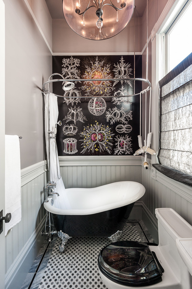 small bathroom with white toilet with black lid, claw feet black tub with white inside with curtain, white wall, white and black tiles