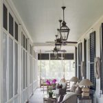 Traditional Porch With Glass Window Screen, Rattang Chairs With Nude Cushion, Wooden Swing With White Cushion, Glass Top Ratta Coffee Table And Side Tables
