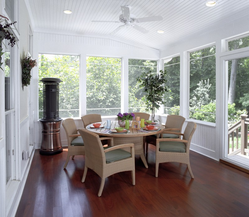 traditional porch with white wooden ceiling and window framed, brown wooden flooring, brown rattan chairs surround round rattan table with wood top