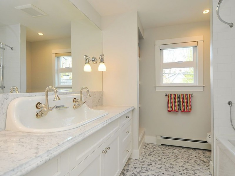 white curvy trough sink with double faucets installed inside the higher area of the sink