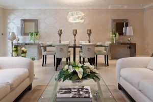 white elegant living area with white sofa, glass coffee table, pale brown rug and dinign area with white leather chairs with glass top table, glamorous pendant lamp